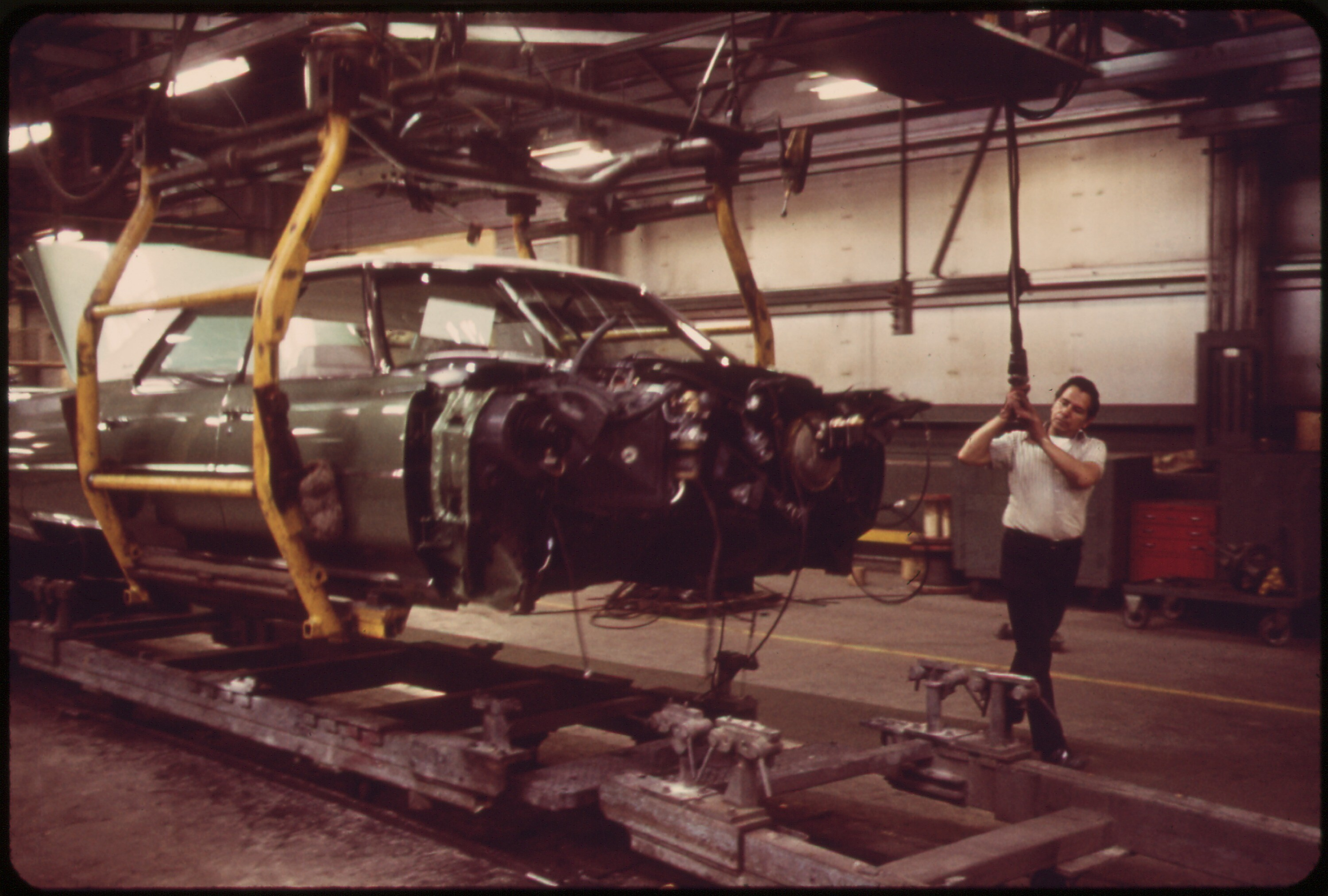 ON_THE_CADILLAC_ASSEMBLY_LINE-WIRING_IS_COMPLETE_ON_THIS_BODY,_AND_NOW_THE_WORKER_WILL__DROP__IT_THR